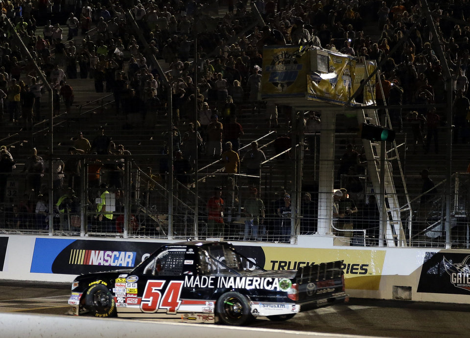 Photo - Darrell Wallace Jr. takes the checkered flag to win the NASCAR Truck Series auto race at Gateway Motorsports Park on Saturday, June 14, 2014, in Madison, Ill. (AP Photo/Jeff Roberson)