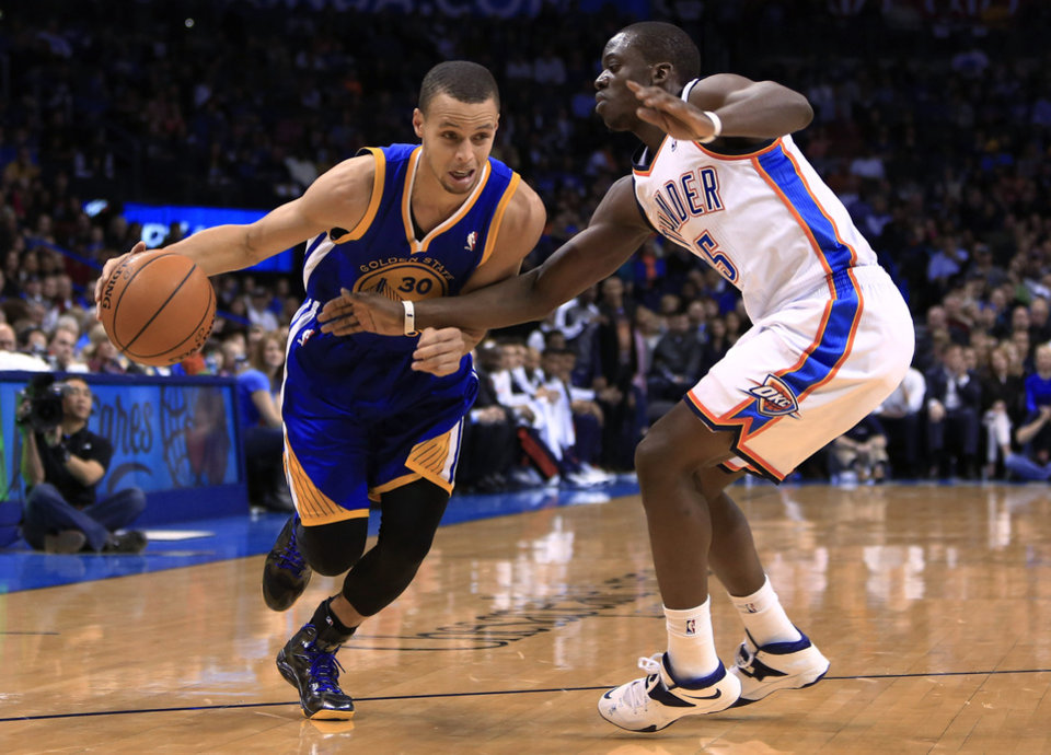 Photo - Golden State Warriors point guard Stephen Curry (30) drives to the basket around Oklahoma City Thunder guard Reggie Jackson (15) during the first quarter of an NBA basketball game Friday, Jan. 17, 2014, in Oklahoma City. (AP Photo/Alonzo Adams)