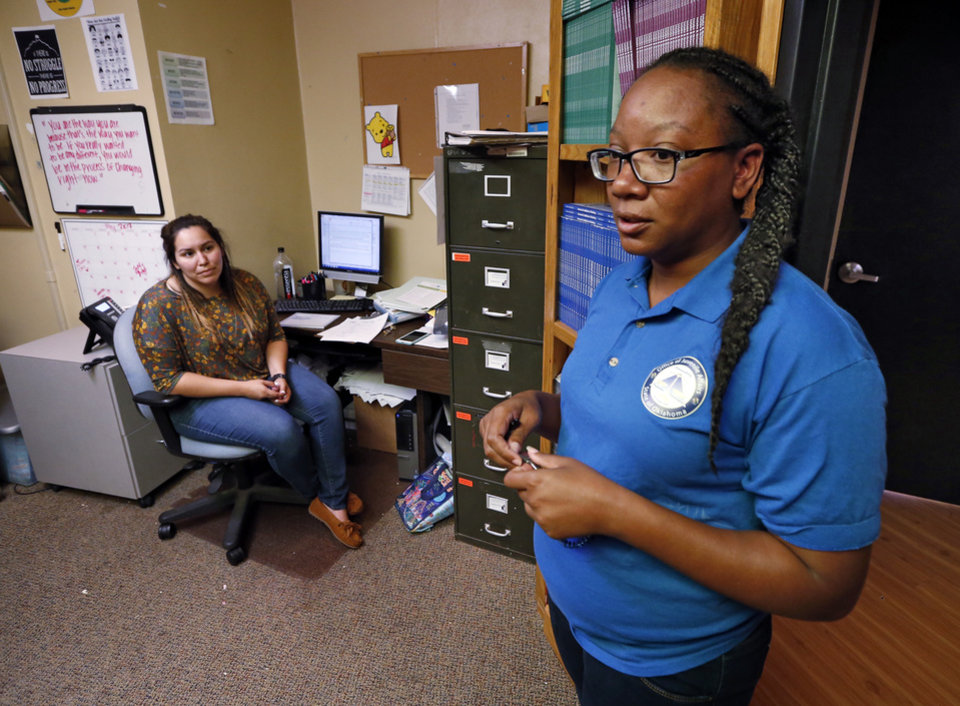 Photo -  Shanorma Stewart, a youth guidance specialist at the Oklahoma Juvenile Center for Girls in Norman, gives a tour while counselor Leslie Hebert sits at her desk. [Photo by Steve Sisney, The Oklahoman]