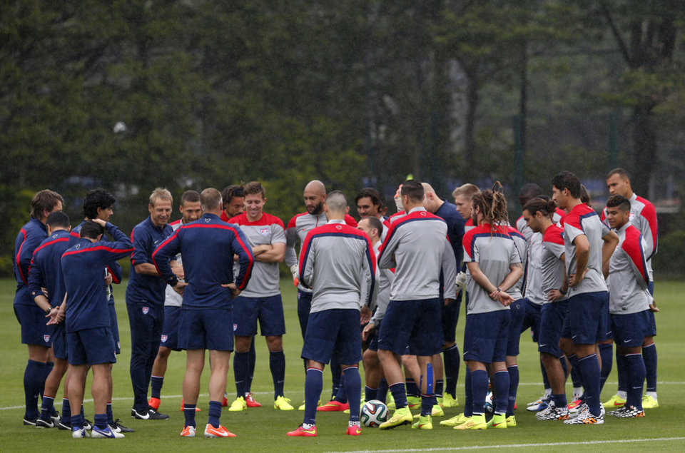 Photo - United States head coach Juergen Klinsmann, fifth from left, addresses his team during a training session at the Sao Paulo FC training center in Sao Paulo, Brazil, Tuesday, June 10, 2014. Klinsmann arrived in Brazil on Tuesday, a day after the team's arrival, because he stayed behind in Miami to watch a friendly between Ghana and South Korea. The U.S. will play against Ghana on June 16 in group G of the 2014 soccer World Cup. (AP Photo/Julio Cortez)