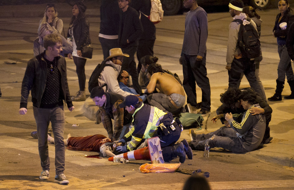 Photo - People are treated after being struck by a vehicle on Red River Street in downtown Austin, Texas, during SXSW on Wednesday March 12, 2014. Police say two people were confirmed dead at the scene after a car drove through temporary barricades set up for the South By Southwest festival and struck a crowd of pedestrians.  (AP Photo/Austin American-Statesman, Jay Janner)