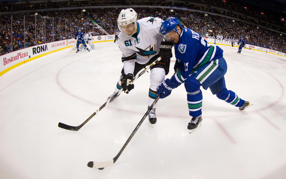 Vancouver Canucks' Henrik Sedin, right, of Sweden, tries to stick handle around San Jose Sharks' Justin Braun during the first period of an NHL hockey game, Thursday, Nov. 14, 2013 in Vancouver, British Columbia.  (AP Photo/The Canadian Press, Darryl Dyck)