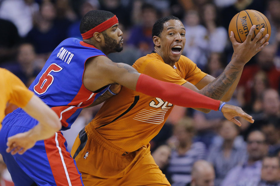 Photo - Detroit Pistons' Josh Smith (6) reaches in as Phoenix Suns' Channing Frye protects the ball during the first half of an NBA basketball game, Friday, March 21, 2014, in Phoenix. (AP Photo/Matt York)