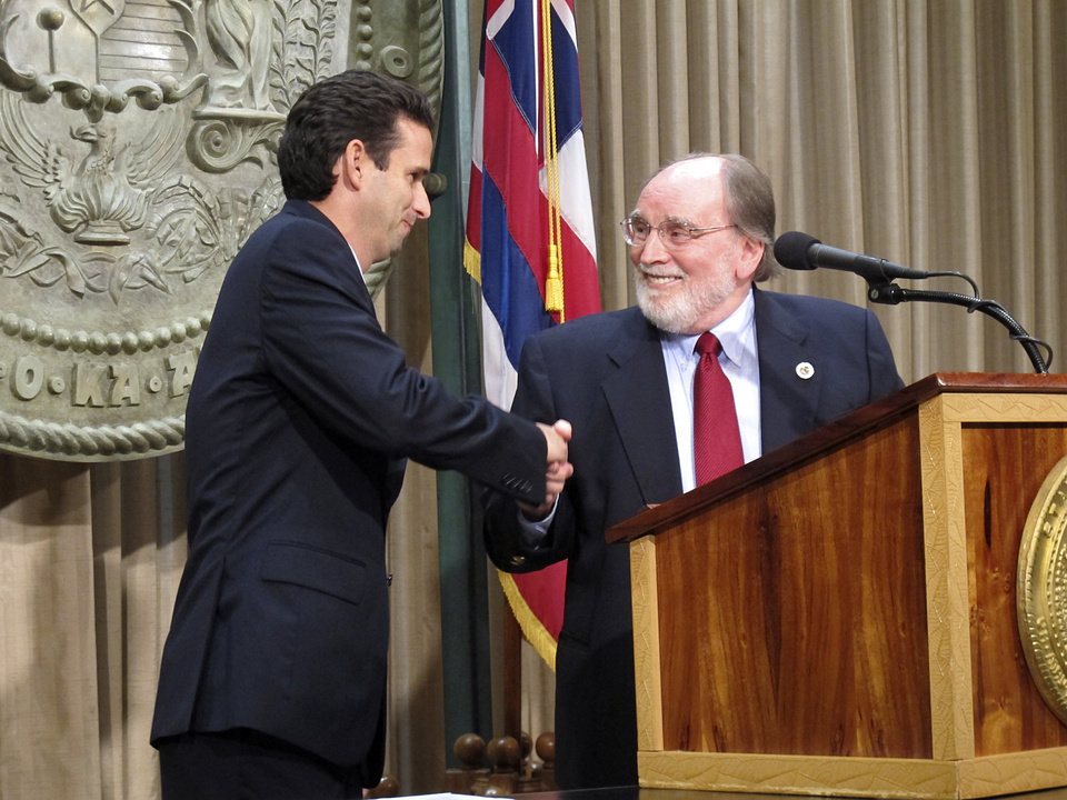 Photo - Hawaii Lt. Gov. Brian Schatz, left, shakes hands with Gov. Neil Abercrombie at the state Capitol in Honolulu on Wednesday, Dec. 26. 2012 after the governor announced he was appointing Schatz to fill the seat vacated by the late U.S. Sen. Daniel Inouye. (AP Photo/Audrey McAvoy)