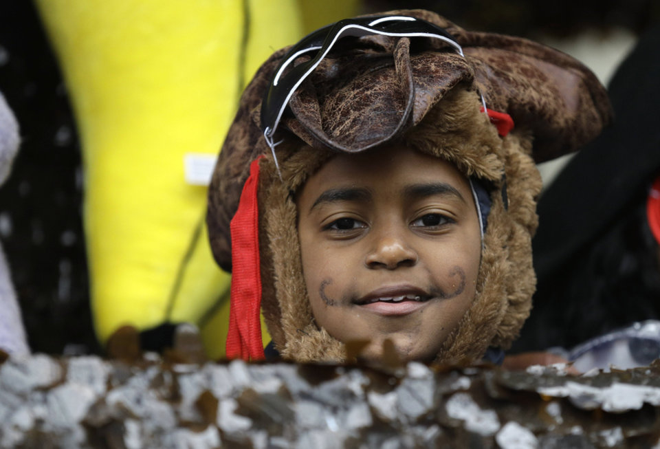 Photo - A child in costume peers from a float in the Krewe of Elks during Mardi Gras in New Orleans, Tuesday, March 4, 2014. Rain and unusually cold temperatures kept most of the normally massive and festive crowds away.  (AP Photo/Gerald Herbert)