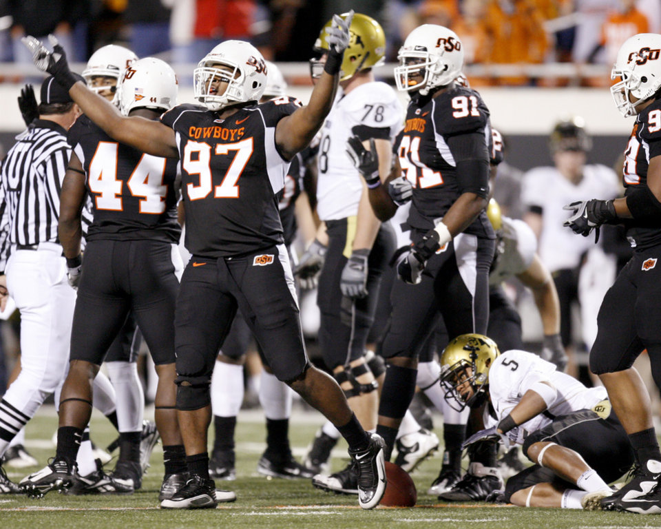 Photo - OSU's Jermiah Price celebrates as Colorado's Rodney Stewart gets up during the college football game between Oklahoma State University (OSU) and the University of Colorado (CU) at Boone Pickens Stadium in Stillwater, Okla., Thursday, Nov. 19, 2009. Photo by Bryan Terry, The Oklahoman