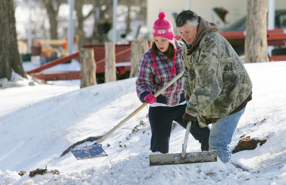 Photo - Miranda Stroud and Dan Erwin clear their driveway on E Harrison in Guthrie, February  3 , 2011. Photo by Steve Gooch, The Oklahoman