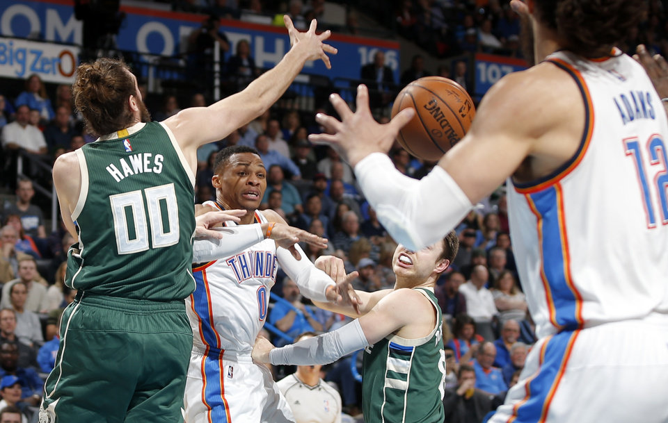 Photo - Oklahoma City's Russell Westbrook (0) passes the ball as Milwaukee's Spencer Hawes (00) defends during an NBA basketball game between the Oklahoma City Thunder and the Milwaukee Bucks at Chesapeake Energy Arena in Oklahoma City, Tuesday, April 4, 2017. Photo by Bryan Terry, The Oklahoman