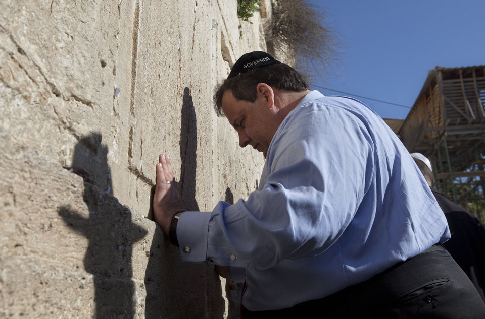 Photo -   New Jersey Gov. Chris Christie touches the stones of the Western Wall, the holiest site where Jews can pray, during his visit to Jerusalem's old city, Monday, April 2, 2012. Christie kicked off his first official overseas trip Monday meeting Israel's leader in a visit that may boost the rising Republican star's foreign policy credentials ahead of November's presidential election. (AP Photo/Sebastian Scheiner)