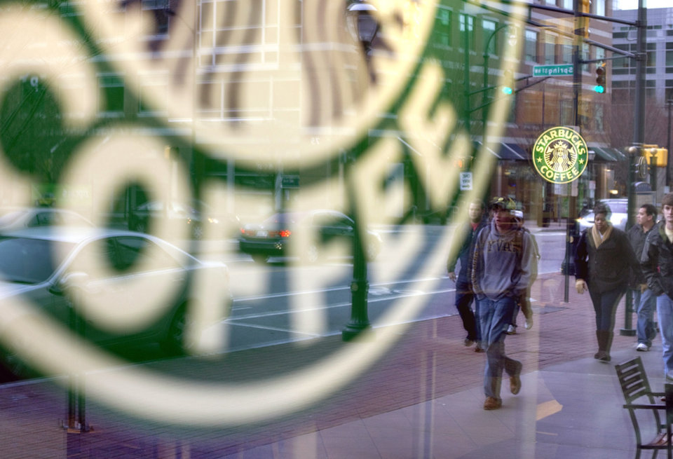FILE - In this Wednesday, Jan. 26, 2011, file photo, pedestrians are reflected outside a Starbucks store in Atlanta. Starbucks, the world\'s biggest coffee company, is planning to add at least 1,500 cafes in the U.S. over the next five years. The plan, which would boost the number of Starbucks cafes in the country by about 13 percent, was announced at the company\'s investor day in New York,Wednesday. Taking into account Canada and South America, the company plans to add a total of 3,000 new cafes in its broader Americas region. (AP Photo/David Goldman, File)