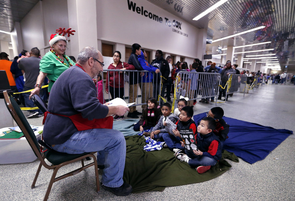Photo -  Linda Sacol, left, and Denis Gozlan read to children waiting in line during the annual Red Andrews Christmas Dinner. [Photo by Steve Sisney, The Oklahoman]