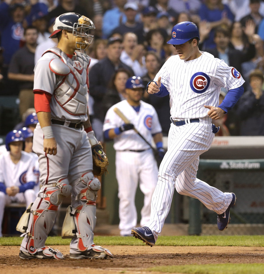 Photo - Chicago Cubs' Anthony Rizzo, right, scores on a single hit by Starlin Castro as Washington Nationals catcher Wilson Ramos looks to the field during the fourth inning of a baseball game in Chicago, Thursday, June 26, 2014. (AP Photo/Nam Y. Huh)