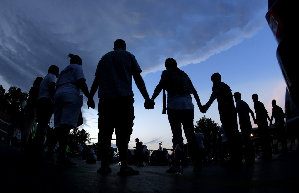 Photo - People stand in prayer after marching about a mile to the police station to protest the shooting of Michael Brown Wednesday, Aug. 20, 2014, in Ferguson, Mo. Brown's shooting in the middle of a street Aug 9, by a Ferguson policeman has sparked a more than week of protests, riots and looting in the St. Louis suburb. (AP Photo/Charlie Riedel)