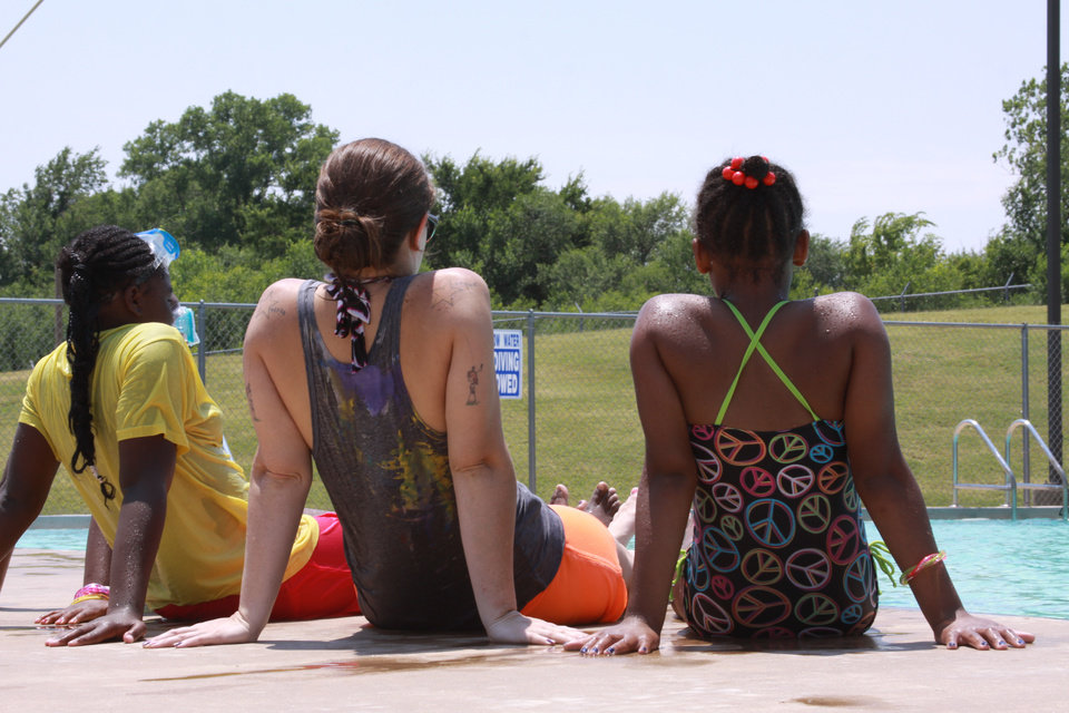 Photo -  Children relax with a camp counselor by the pool at Harvest Foster Kids Camp, which is held each summer at Church of the Harvest, 6800 N Bryant Ave. Photo Provided       Photographer:;Amber Wilkes