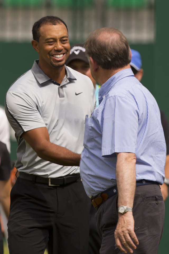 Photo - Tiger Woods of the US walks, left, smiles as he shakes hands with Peter Dawson, Chief Executive of The R&A, on the 1st fairway during a practice round at the Royal Liverpool Golf Club prior to the start of the British Open Golf Championship, in Hoylake, England, Saturday, July 12, 2014. The 2014 Open Championship starts on Thursday, July 17. (AP Photo/Jon Super)