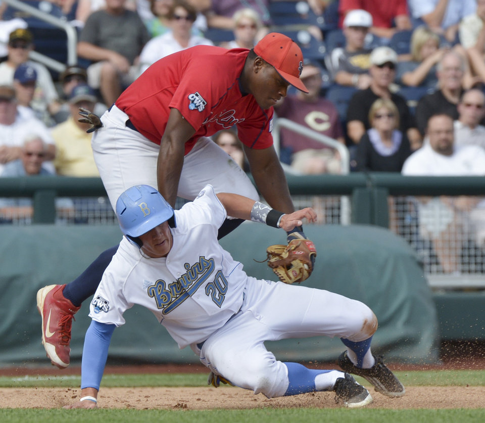 Photo -   UCLA's Jeff Gelalich (20) is tagged out by Stony Brook third baseman William Carmona, in a rundown between second and third base on an attempted stolen base in the second inning of an NCAA College World Series baseball game in Omaha, Neb., Friday, June 15, 2012. (AP Photo/Ted Kirk)