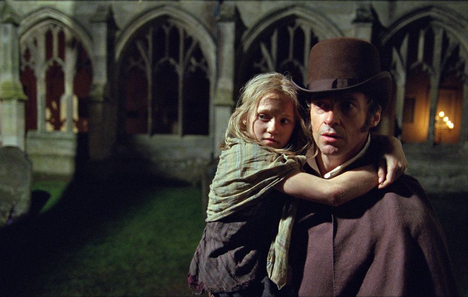 This film image released by Universal Pictures shows Hugh Jackman as Jean Valjean holding Isabelle Allen as Young Cosette in a scene from