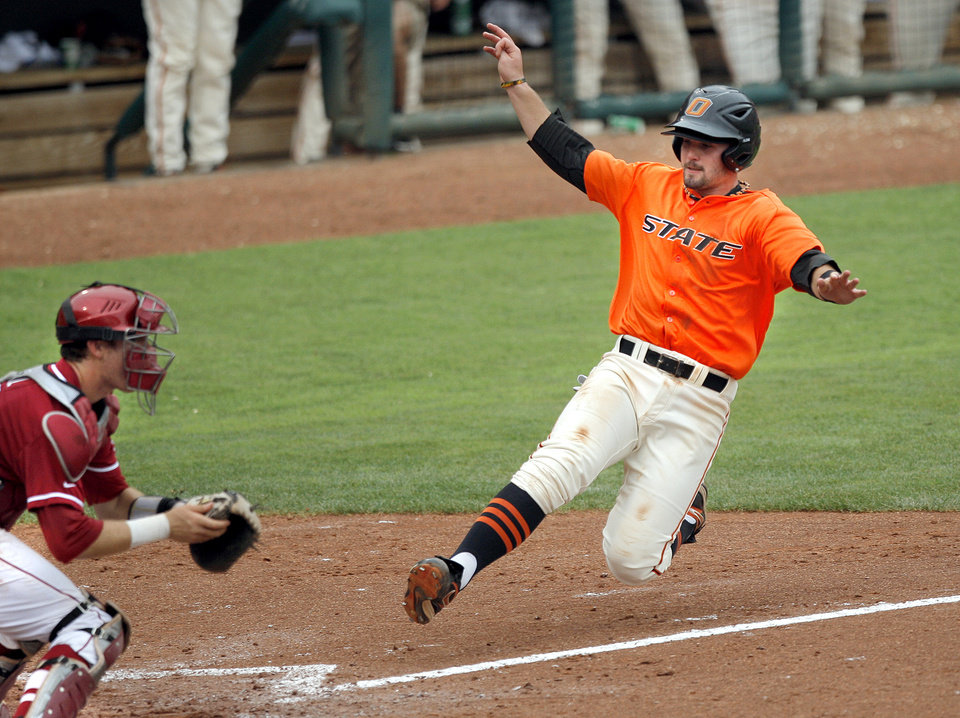 Oklahoma State's Robbie Rea slides safely into home as Oklahoma's Dylan Neal waits for the throw during the Bedlam baseball game between the University of Oklahoma and Oklahoma State University at the Chickasaw Bricktown Ballpark in Oklahoma City, Sunday, May 6, 2012. Photo by Sarah Phipps, The Oklahoman