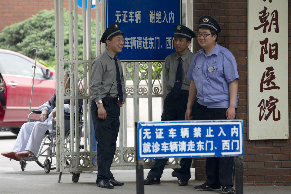 Photo -   Security guards chat at an entrance of the hospital where blind activist Chen Guangcheng is staying for treatment in Beijing Monday, May 7, 2012. The Chinese activist who triggered a diplomatic dispute between China and the United States said Monday he was confident that Beijing would hold up its end of a tentative deal to let him study overseas. (AP Photo/Alexander F. Yuan)