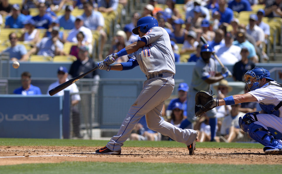 Photo - New York Mets' Ruben Tejada, left, hits a two-run home run as Los Angeles Dodgers catcher A.J. Ellis, right, looks on during the third inning of a baseball game, Sunday, Aug. 24, 2014, in Los Angeles. (AP Photo/Mark J. Terrill)