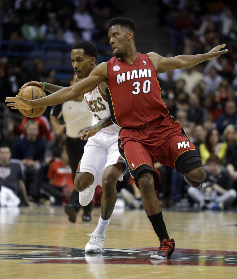 Photo - Milwaukee Bucks' Brandon Jennings, left, tries to drive past Miami Heat's Norris Cole (30) during the second half of Game 3 in their first-round NBA basketball playoff series on Thursday, April 25, 2013, in Milwaukee. (AP Photo/Morry Gash)