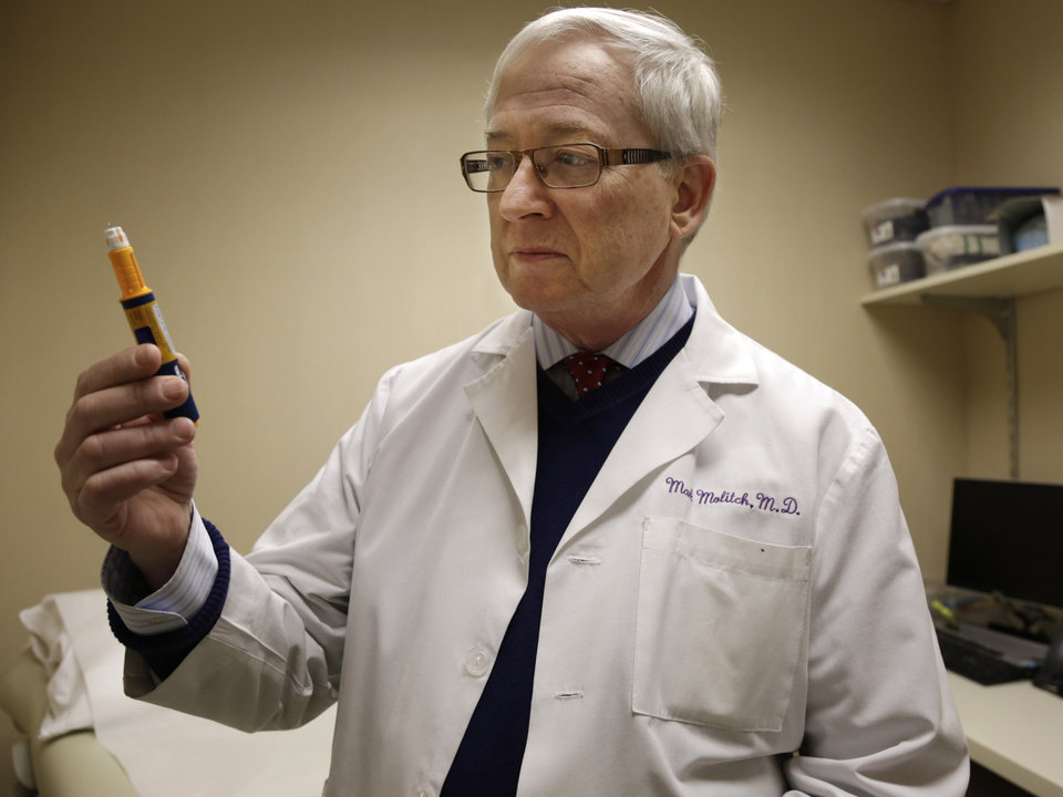 Dr. Mark Molitch of Northwestern University, who helped write medical standards meant to limit HGH treatment to legitimate patients, holds an injector pen that contains approximately a weeks worth of doses for a patient in need of the drug at his clinic Thursday, Dec. 20, 2012, in Chicago. An Associated Press investigation shows that a federal crackdown on illicit foreign supplies of human growth hormone has failed to stop rampant misuse, and instead has driven record sales of the drug by some of the world's biggest pharmaceutical companies. (AP Photo/M. Spencer Green)