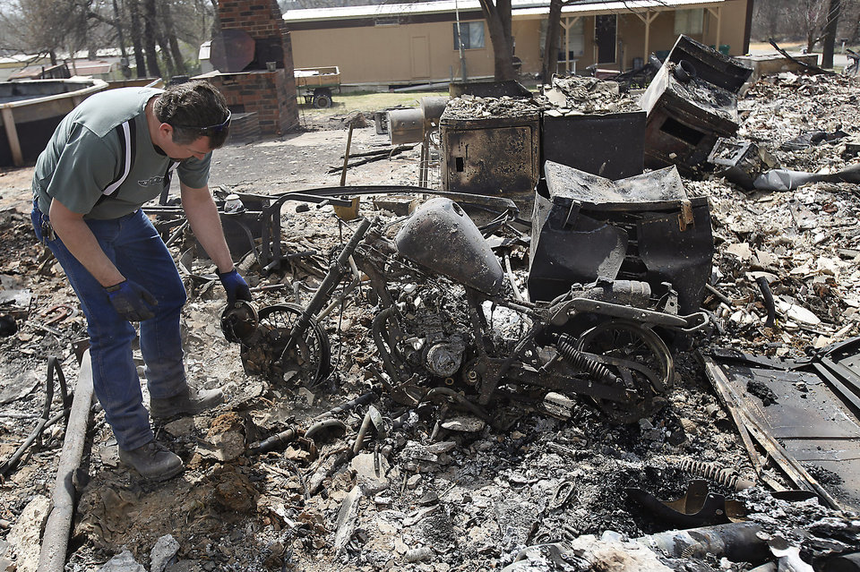 Photo - George West looks for anything left to a motorcycle that might be salvageable in the remains of a house that was destroyed by wildfires on Friday, April 10, 2009, in Choctaw, Okla.  Photo by Chris Landsberger, The Oklahoman
