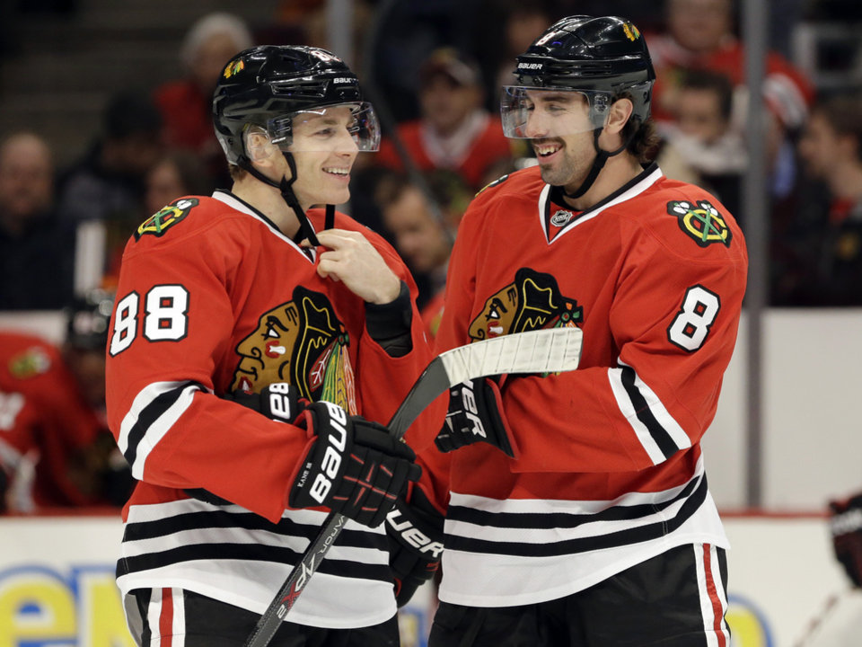 Photo - Chicago Blackhawks' Patrick Kane, left, smiles as he talks with Nick Leddy (8) during the first period of an NHL hockey game against the Phoenix Coyotes in Chicago, Thursday, Nov. 14, 2013. (AP Photo/Nam Y. Huh)