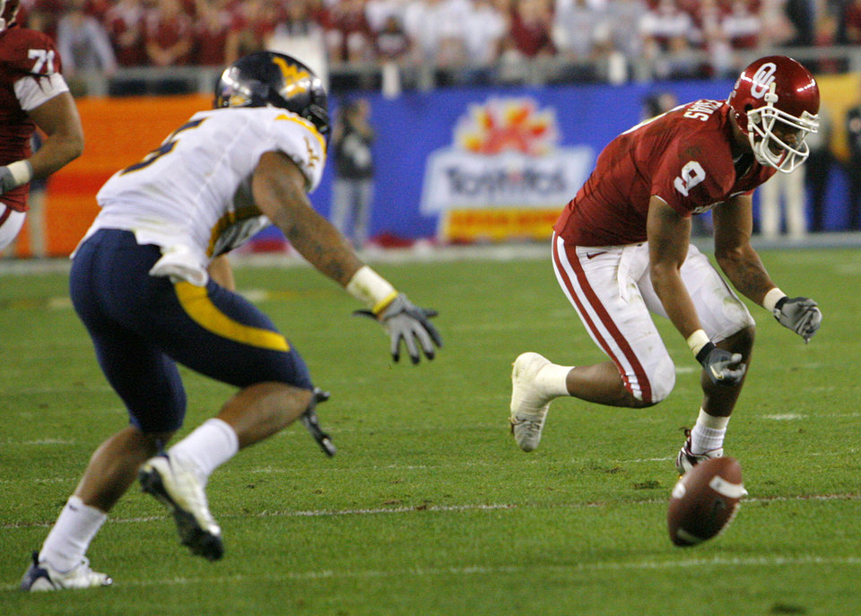 Photo - Oklahoma's Juaquin Iglesias (9) drops a pass in front of West Virginia's Antionio Lewis (6) during the first half of the Fiesta Bowl college football game between the University of Oklahoma Sooners (OU) and the West Virginia University Mountaineers (WVU) at The University of Phoenix Stadium on Wednesday, Jan. 2, 2008, in Glendale, Ariz. 