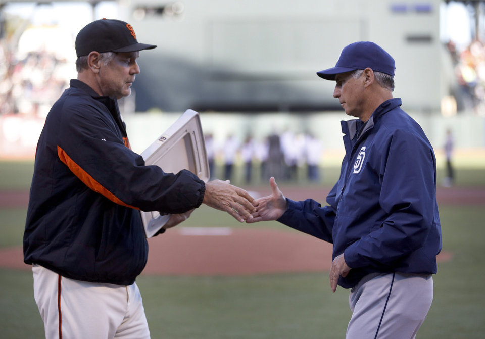 Photo - San Francisco Giants manager Bruce Bochy, left, shakes hands with San Diego Padres manager Bud Black, left, as he offers his a baseball plate in memory of former San Diego Padres baseball player Tony Gwynn before the start of a baseball game in San Francisco, Monday, June 23, 2014. Gwynn died of cancer at the age of 54. (AP Photo/Tony Avelar)