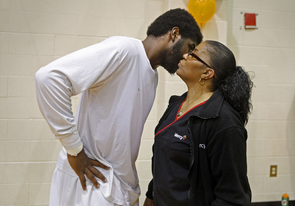 Photo - Dorshell Clark kisses her son, Deondre Clark, on the cheek after his basketball game at Douglass High School in Oklahoma City, Tuesday, January 28, 2014. Photo by Bryan Terry, The Oklahoman