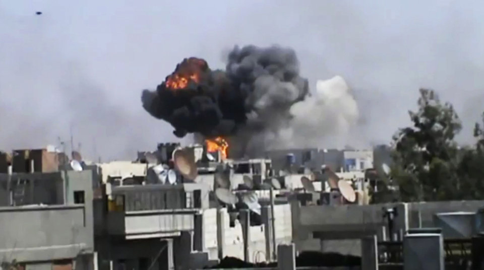 Photo -   In this image made from amateur video released by the Shaam News Network and accessed Wednesday, April 18, 2012, smoke billows an impact following purported shelling in Khaldiyeh district, Homs, Syria. Nearly a week after a cease-fire took effect, Syrian troops pounded a rebel stronghold Wednesday as the country's foreign minister met with his Chinese counterpart in Beijing during the latest round of talks aimed at preventing the truce from unraveling. (AP Photo/Shaam News Network via AP video) TV OUT, THE ASSOCIATED PRESS CANNOT INDEPENDENTLY VERIFY THE CONTENT, DATE, LOCATION OR AUTHENTICITY OF THIS MATERIAL