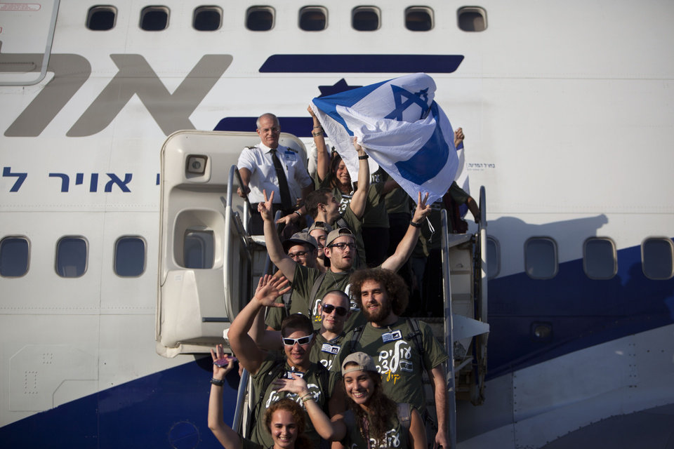 New Jewish immigrants from U.S. wave an Israeli flag as they arrive at the Ben Gurion airport near Tel Aviv, Israel, Tuesday, Aug. 14, 2012. A total of 350 immigrants arrived on the flight from the U.S. Tuesday, and were welcomed by Israel's Prime Minister Benjamin Netanyahu in a ceremony at the airport. Over 100 of the new immigrants are expected to join the Israel Defense Forces in the upcoming month. (AP Photo/Oded Balilty)