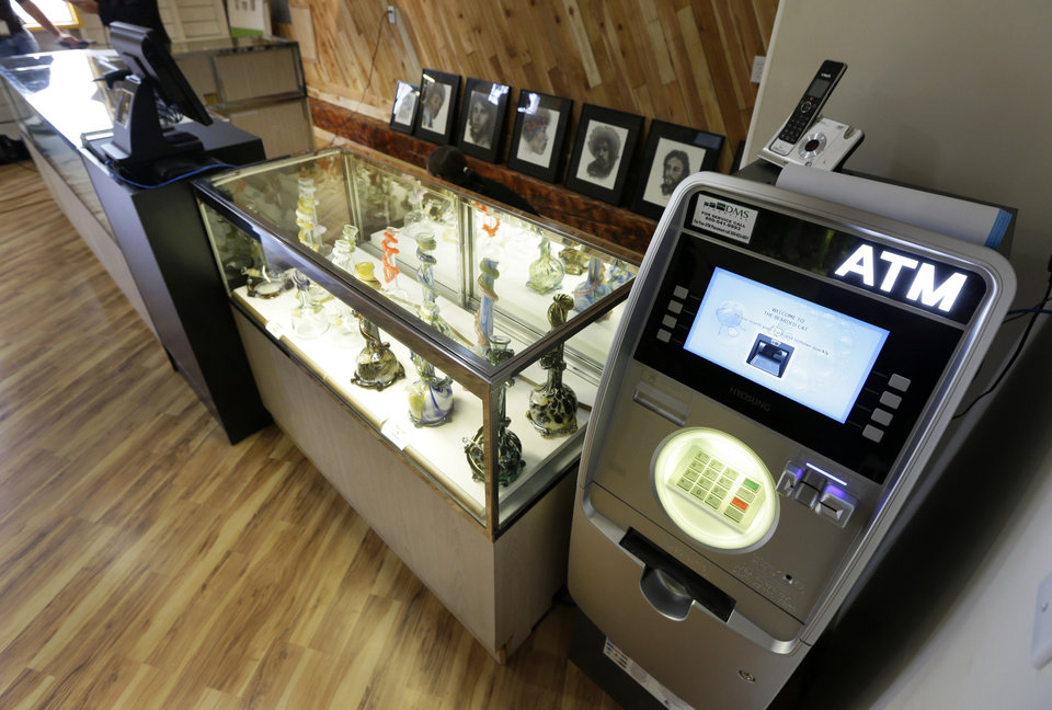 Photo - An ATM sits next to a case displaying glass bongs, Monday, July 7, 2014 at the recreational marijuana store Cannabis City in Seattle. When legal sales begin on Tuesday, July 8, 2014, the store will be the first and only store in Seattle to initially sell recreational marijuana. (AP Photo/Ted S. Warren)