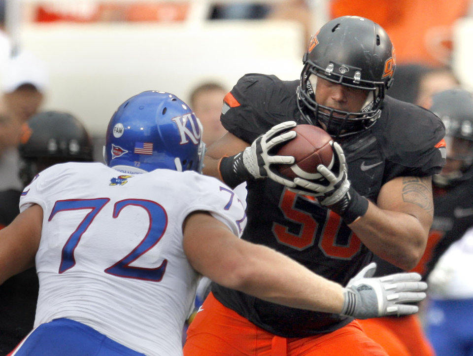 Photo - Oklahoma State's Jamie Blatnick (50)intercepts a pass as Kansas' Tanner Hawkinson (72) defends during the first half of the college football game between the Oklahoma State University Cowboys (OSU) and the University of Kansas Jayhawks (KU) at Boone Pickens Stadium in Stillwater, Okla., Saturday, Oct. 8, 2011. Photo by Sarah Phipps, The Oklahoman