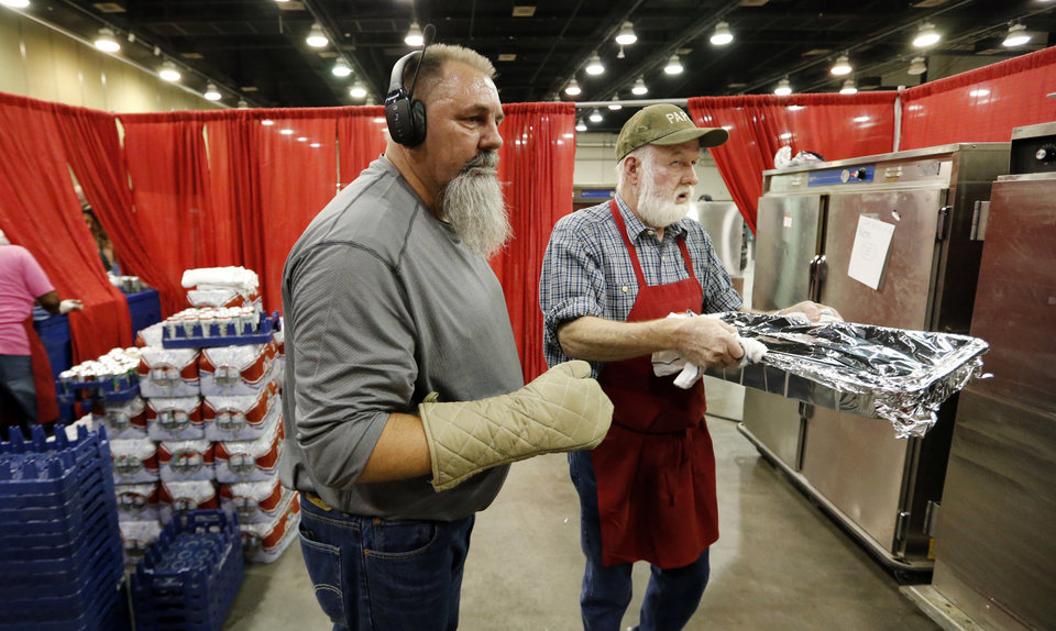 Photo - Kitchen manager Chris Cheffer, left, directs traffic in the food prep area during the annual Red Andrews Christmas Dinner in the Cox Convention Center on Monday, Dec. 25, 2017 in Oklahoma City, Okla.  Cheffer has worked at the event 22 years and Rick Forehand, Moore, (right) has worked over 12 years.  Photo by Steve Sisney, The Oklahoman