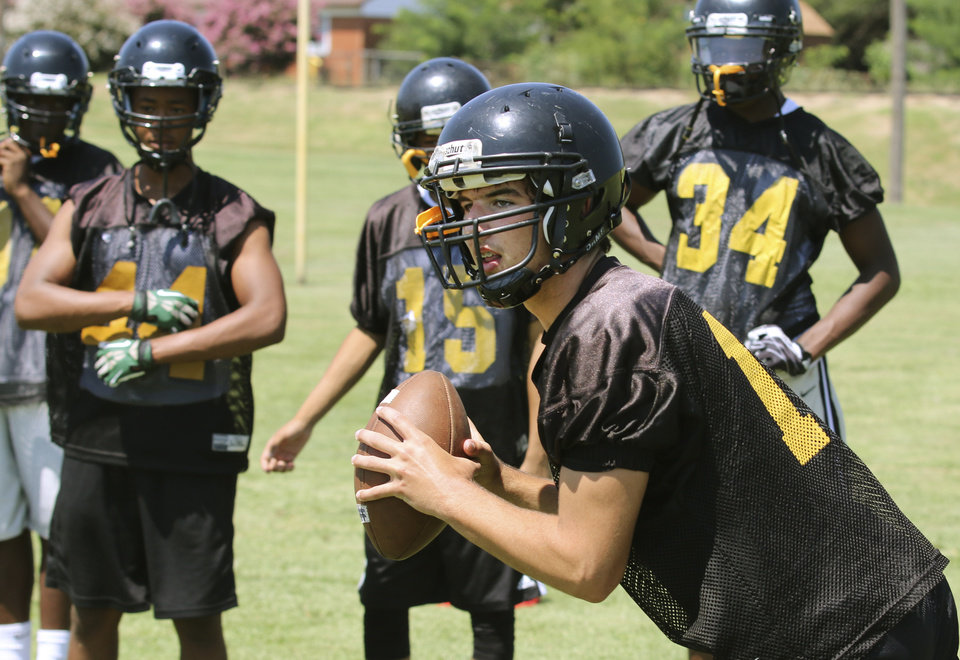 Photo - Midwest City's Brendan Brown looks for a receiver during practice in Midwest City, Tuesday  August  12, 2014. Photo By Steve Gooch, The Oklahoman