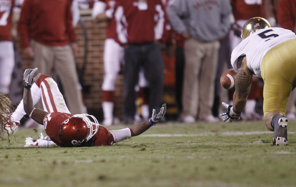 Photo -   Oklahoma receiver Jalen Saunders (18) bobbles a pass into the hands of Notre Dame linebacker Manti Te'o (5) in the fourth quarter of an NCAA college football game in Norman, Okla., Saturday, Oct. 27, 2012. Notre Dame won 30-13. (AP Photo/Sue Ogrocki)