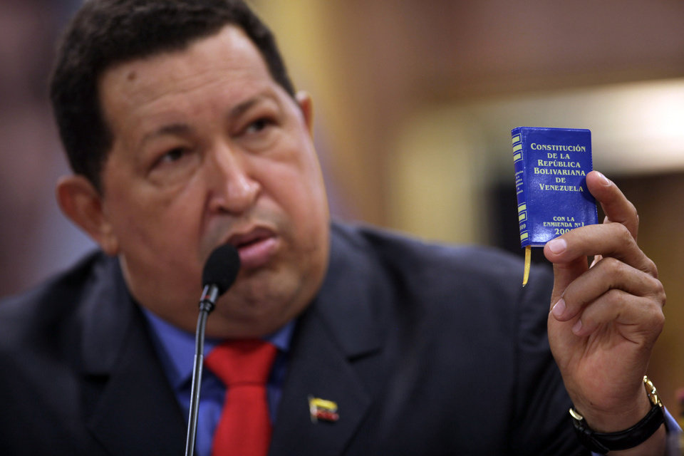 Venezuela's President Hugo Chavez holds up a miniature copy of Venezuela's constitution during a press conference at the Miraflores palace in Caracas, Venezuela, Tuesday, Oct. 9, 2012. The 58-year-old former military officer Chavez won his fourth consecutive presidential bid Sunday and shows no signs of ballot fatigue. (AP Photo/Rodrigo Abd)