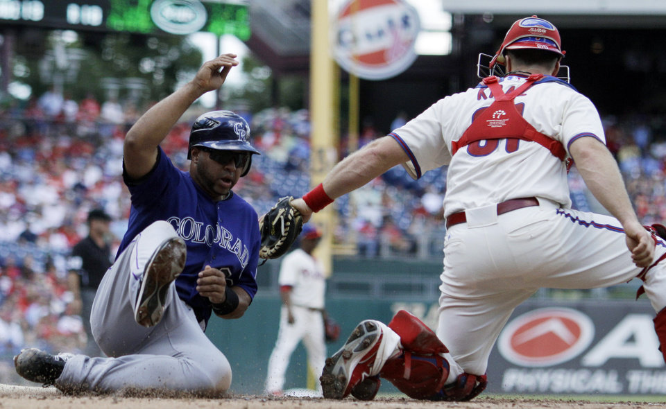 Photo -   Colorado Rockies' Wilin Rosario, left, scores past Philadelphia Phillies catcher Erik Kratz on a single by DJ LeMahieu in the second inning of the first game of a baseball doubleheader on Sunday, Sept. 9, 2012, in Philadelphia. (AP Photo/Matt Slocum)