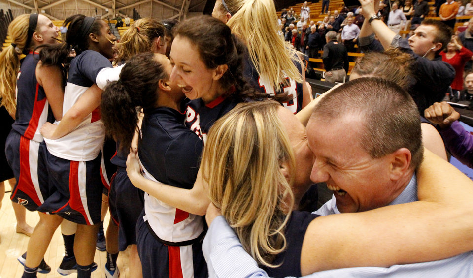 Photo - Penn head coach Mike McLaughlin, right, celebrates with assistant coach Bernadette Laukaitis after his team beat Princeton 80-64 after an NCAA college basketball game, Tuesday, March 11, 2014, in Princeton, N.J. The victory gives Penn the Ivy League title. (AP Photo/Julio Cortez)