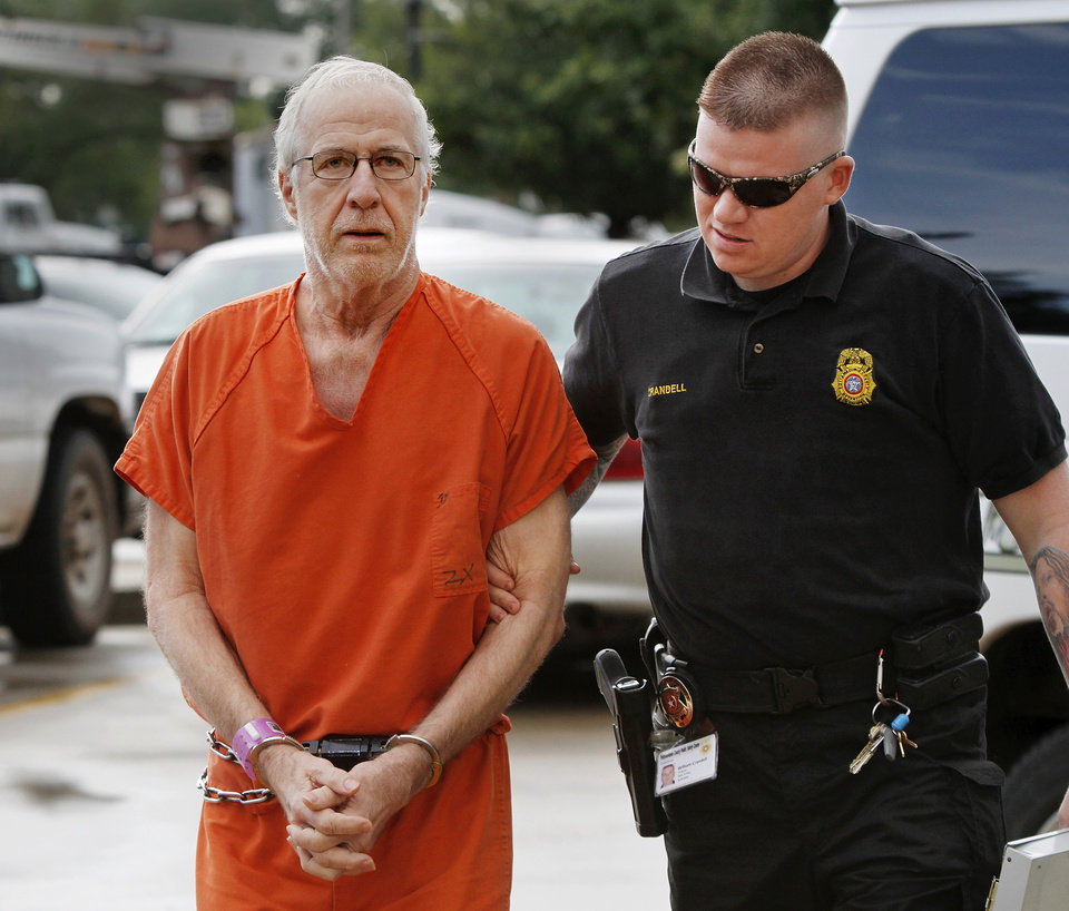 Photo - Former McLoud school teacher Kim Crain and her alleged accomplice, Gary Doby, a former professor at OBU, shown here being escorted by Pottawatomie County Deputy William Crandell,  arrive at the  Pottawatomie County Courthouse Monday morning, May 21, 2012,  for a preliminary hearing. Photo by Jim Beckel, The Oklahoman
