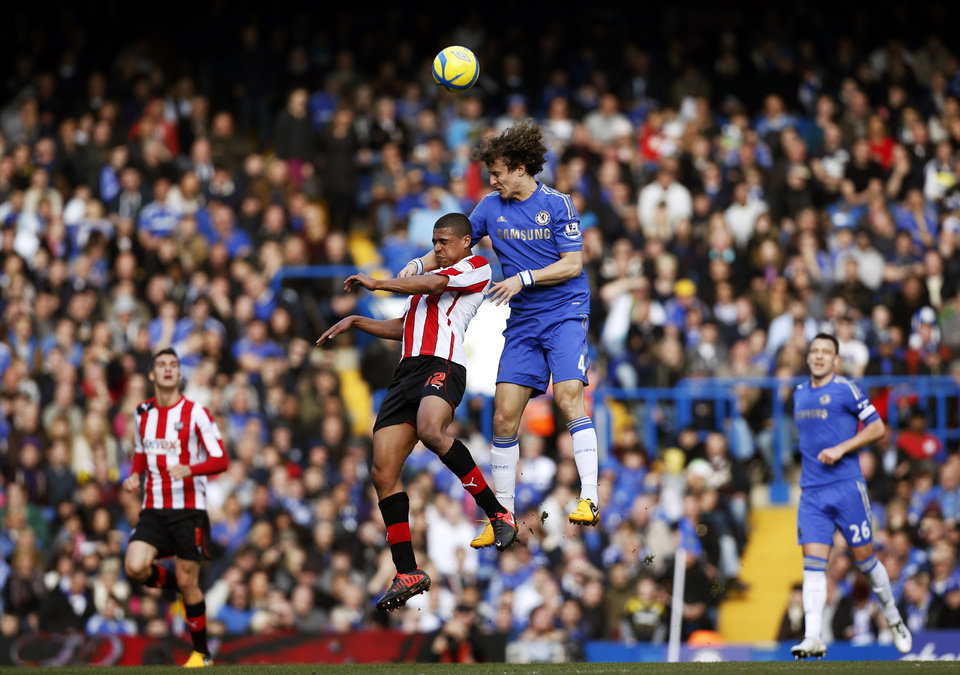 Photo - Chelsea's David Luiz, centre right, competes for the ball with Brentford's Tom Adeyemi during the English FA Cup fourth round replay soccer match between Chelsea and Brentford,  at Stamford Bridge stadium in London, Sunday, Feb. 17, 2013.  (AP Photo/Matt Dunham)