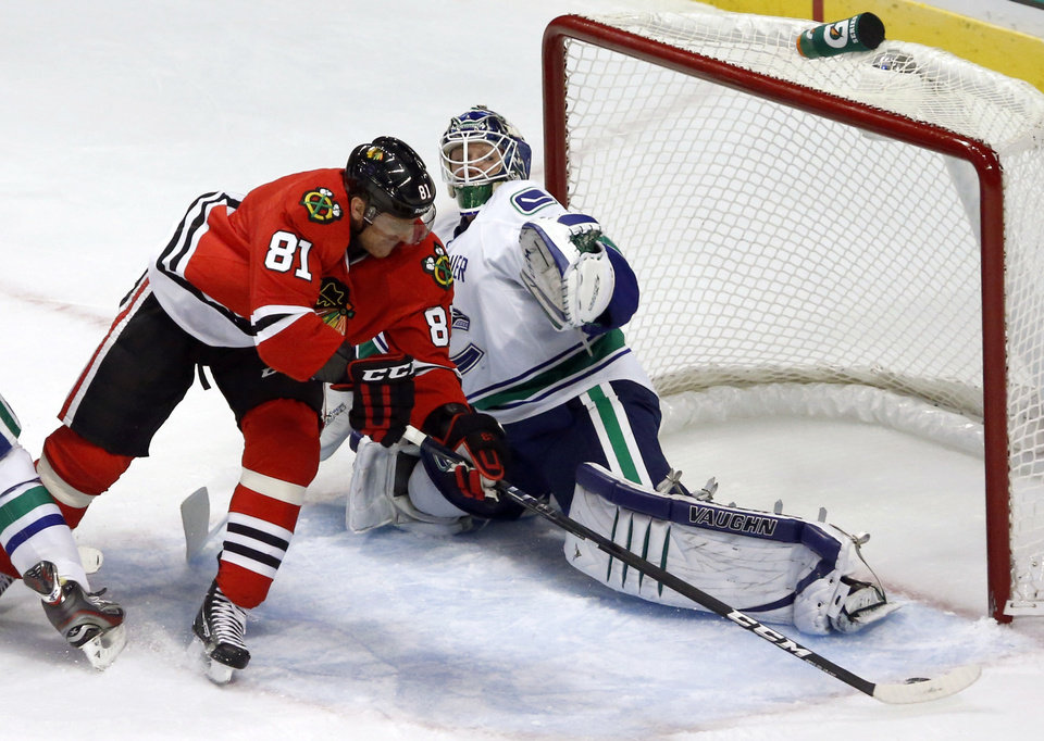 Photo - Chicago Blackhawks right wing Marian Hossa (81), from Slovakia, skates past Vancouver Canucks goalie Cory Schneider to score his second goal in the second period of an NHL hockey game Tuesday, Feb. 19, 2013 in Chicago. (AP Photo/Charles Rex Arbogast)