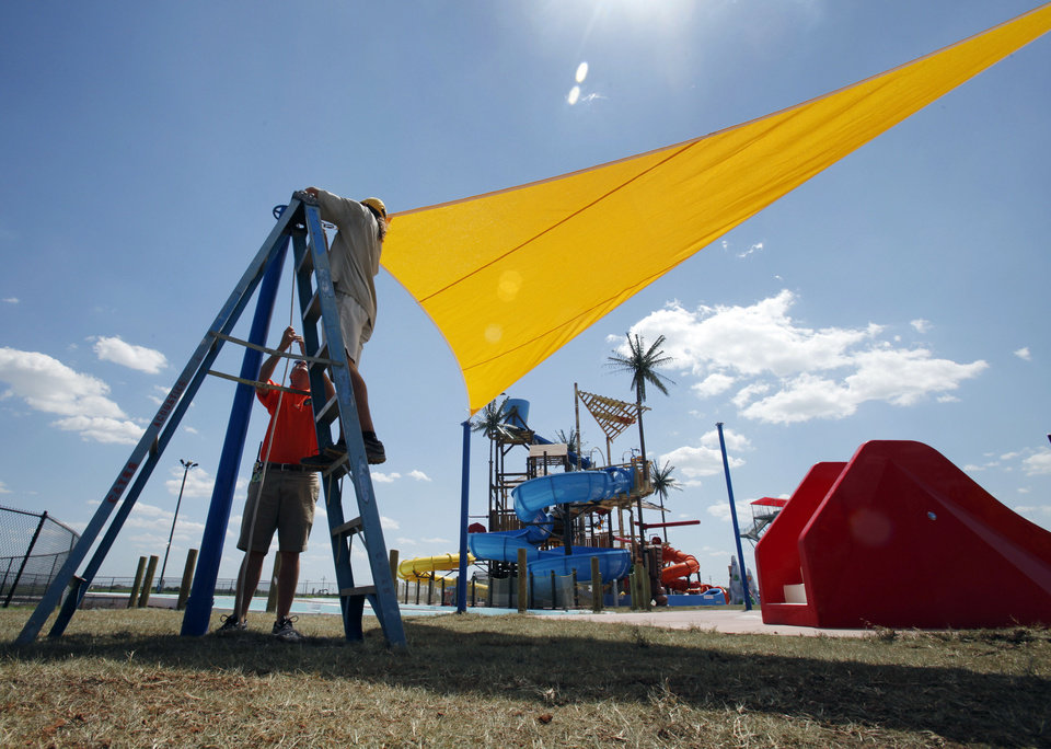 Workers hang banners at Andy Alligator's Water Park off Interstate 35 at Indian Hills Road in Norman in preparation for opening day. PHOTO BY STEVE SISNEY, THE OKLAHOMAN <strong>STEVE SISNEY</strong>