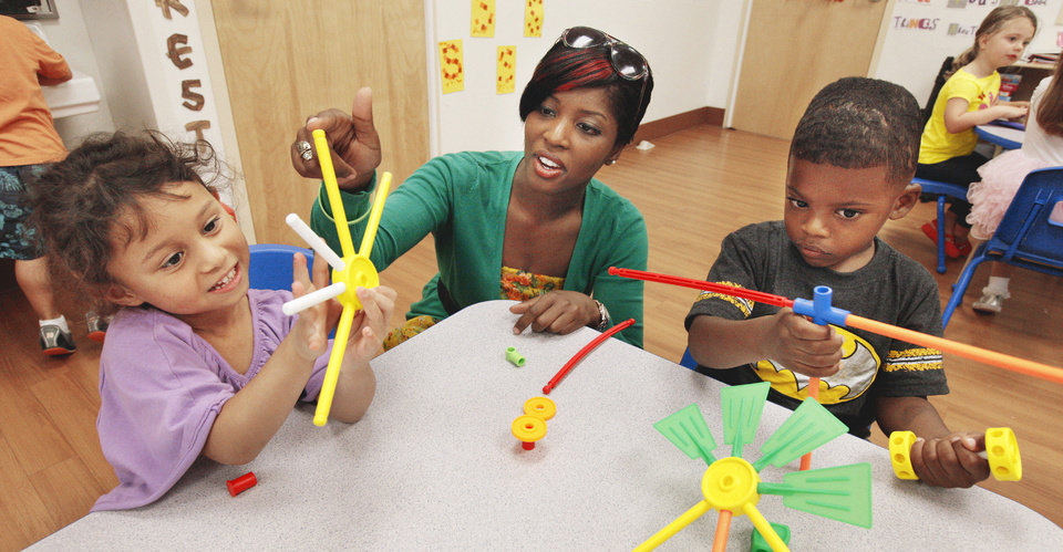 Photo - (Ed Note: school does not give out last names)  Pre-K teacher Kayla Eleby works with students Angelina, and Quincy, both age 4,  as they play with Tinker Toys at The Goddard School on Western Ave. in Oklahoma City as students get to try out  new toys during the 2013 Goddard School Preschooler Approved Toy Test Thursday, Oct. 3, 2013. Students get to try out new toys that encourage interactive play before the toys are released in stores. Photo by Paul B. Southerland, The Oklahoman