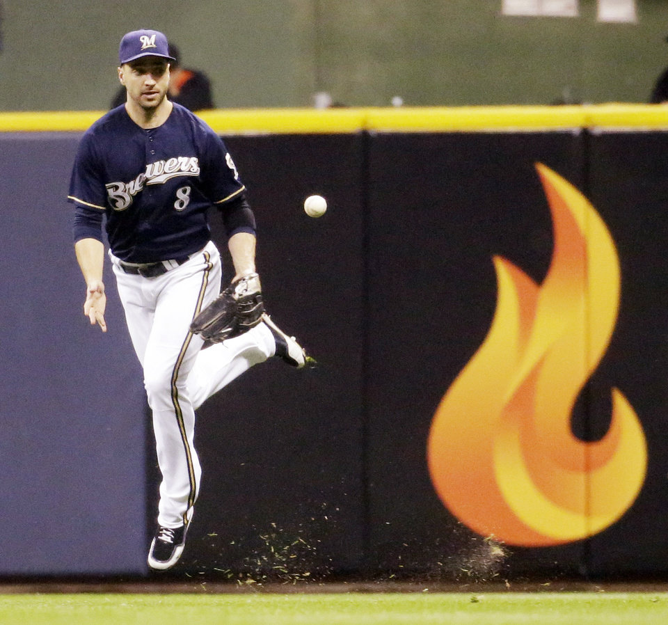 Photo - Milwaukee Brewers' Ryan Braun can't catch a ball hit by San Francisco Giants' Joe Panik during the sixth inning of a baseball game Tuesday, Aug. 5, 2014, in Milwaukee. (AP Photo/Morry Gash)