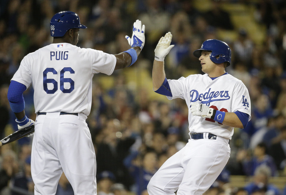 Photo - Los Angeles Dodgers' Tim Federowicz, right, high-fives Yasiel Puig after he scored on a sacrifice hit by Carl Crawford during the fifth inning of a baseball game against the Philadelphia Phillies on Tuesday, April 22, 2014, in Los Angeles. (AP Photo/Jae C. Hong)