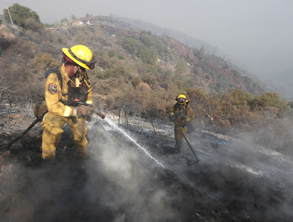Photo - In this Aug. 23, 2012 file photo, firefighter Dennis  Navle, left, hoses down a smoking log as he and Robert Smith extingush hot spots of the Ponderosa Fire near Paynes Creek,  Calif.  A fire-prevention fee  is back before the state Legislature, as Gov. Jerry Brown proposes to expand it us and proponents try to kill it.(AP Photo/Rich Pedroncelli, file)