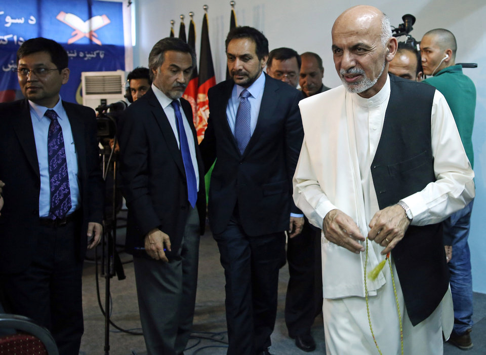 Photo - Afghan presidential candidate Ashraf Ghani Ahmadzai, right, leaves a news conference in Kabul, Afghanistan, Tuesday, July 8, 2014. Ahmadzai welcomed the announcement of the preliminary results of election on Monday. (AP Photo/Massoud Hossaini)